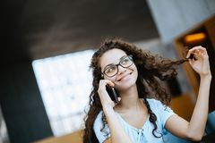 Het leuke Braziliaanse meisje met krullend haar heeft een grappig en opwindend gesprek op de telefoon stock fotografie