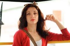 Het leuke brunette drijft in een tram Rood jasje, close-upportret Stock Afbeeldingen