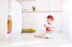 Het leuke de jongen van de gemberbaby spelen met speelgoed in heldere keuken, thuis stock fotografie
