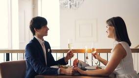 Het leuke de paarmeisje en kerel spreken en het lachen holdingsglazen met mousserende wijn tijdens romantische datum in restauran stock videobeelden