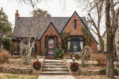 Het leuke die baksteenplattelandshuisje met rood buigt en groen - voor Kerstmis in sombere wintertijd wordt verfraaid stock afbeelding