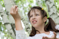 Het leuke donkerbruine meisje houdt gevonden larve Stock Fotografie