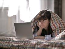 Het leuke donkerbruine meisje ligt onder de dekking en onderzoekt laptop stock foto's