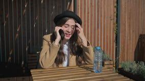 Het leuke donkerbruine spreken op de telefoon in een park stock videobeelden