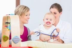 Het leuke en gezonde babymeisje spelen met de stethoscoop tijdens onderzoek stock fotografie