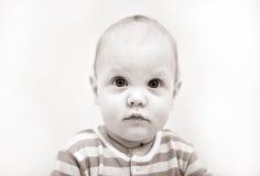 Het leuke ernstige kind met ogen brede open kijkt strai Stock Afbeelding