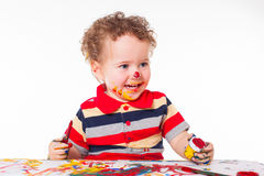 Het leuke gelukkige babyjongen spelen met verven Stock Afbeelding
