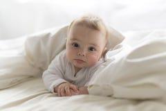Het leuke gelukkige meisje van de 7 maandbaby in en luier die liggen spelen Stock Afbeelding