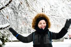 Het leuke het glimlachen jongen spelen met sneeuw royalty-vrije stock afbeelding