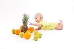 Het leuke glimlachende gezonde kind ligt op een witte achtergrond onder frui Royalty-vrije Stock Foto