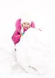 Het leuke glimlachende meisje maakt sneeuwman in de winterdag Royalty-vrije Stock Afbeeldingen