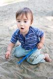 Het leuke jong geitje spelen met zand Royalty-vrije Stock Afbeeldingen