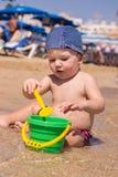 Het leuke jong geitje spelen op het strand met zand en water Stock Afbeelding