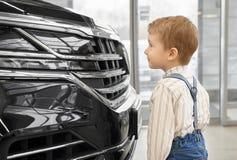 Het leuke jong geitje waarnemen, die dure zwarte auto bekijken royalty-vrije stock foto