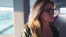 Het leuke jonge blondemeisje in oogglazen draait aan camera en verbetert het Aantrekkelijk nerdy meisje Zijnd positief, vrolijk stock video