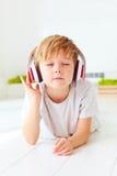 Het leuke jonge geitje luistert aan de muziek, die thuis ontspannen stock afbeeldingen
