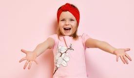 Het leuke jonge geitje van het babymeisje in lichtrose pyjama's en rode hoofdband met opgeheven uitgespreide handen Royalty-vrije Stock Foto's