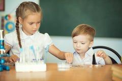 Het leuke jonge geitjes bestuderen, slimme meisje en jongen die het huiswerk doen Stock Fotografie