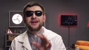 Het leuke jonge mannetje die zonnebril en witte laboratoriumlaag dragen spreekt actief stock footage