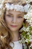 Het leuke jonge meisje met lang blond haar die zich in een weide in kroon die van bloemen bevinden, een boeket van de lente houde Stock Afbeeldingen