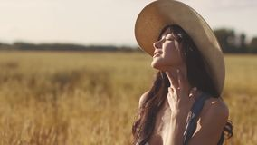 Het leuke jonge meisje raakt haar hals De jonge vrouw geniet van een warme de zomerdag op het gebied stock footage
