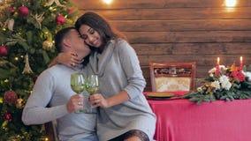 Het leuke jonge paar met wijnglazen zit op achtergrond van spar op vooravond van nieuw jaar stock videobeelden