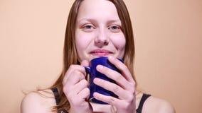 Het leuke jonge tienermeisje drinkt thuis koffie of thee 4k UHD stock videobeelden