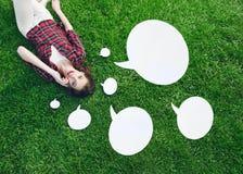Het leuke, jonge vrouw liggen op het gras, die op de celtelefoon spreken met toespraak borrelt Royalty-vrije Stock Foto's