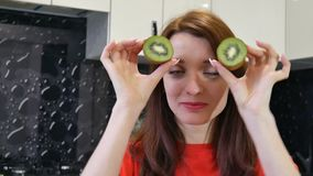 Het leuke jonge vrouw spelen met de twee helften van kiwi terwijl het prepearing van voedsel bij de keuken Positief menselijk emo stock footage