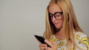 Het leuke jonge vrouw texting op haar telefoon die glazen in studio dragen stock videobeelden