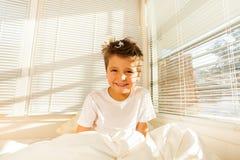 Het leuke jongen awaking in wit slaapkamerhoogtepunt van zonlicht stock afbeeldingen