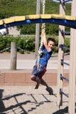 Het leuke jongen hangen op een kabel op speelplaats Stock Foto
