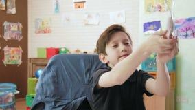 Het leuke jongen spelen met het stuk speelgoed vliegtuig stock videobeelden