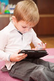 Het leuke jongen spelen met tablet Stock Foto's