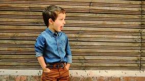 Het leuke jongen stellen tegen blokhuismuur stock videobeelden