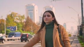 Het leuke Kaukasische meisje met bruine ogen en lang aardig haar probeert de achterstand in te lopen auto terwijl status dichtbij stock footage