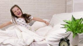 Het leuke kielzog van weinig kindmeisje omhoog van slaap in bed stock footage