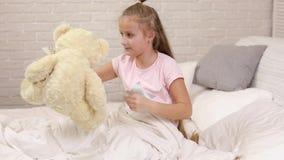 Het leuke kielzog van weinig kindmeisje omhoog van slaap in bed stock videobeelden