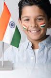 Het leuke kijken Indisch jong geitje met Indische vlag stock afbeeldingen