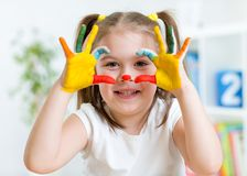 Het leuke kind heeft pret schilderend haar handen Stock Foto's