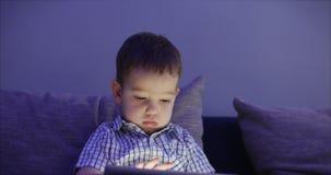 Het leuke Kind Onderhouden met Tablet Little Boy die Vrije tijd doorbrengen die Mobiel Spel in en Verbrijzeling spelen Helder stock video