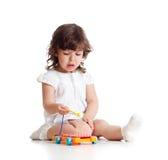 Het leuke kind spelen met muzikaal stuk speelgoed Stock Afbeeldingen