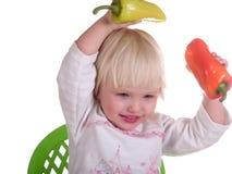 Het leuke kind werpt peper Stock Foto's