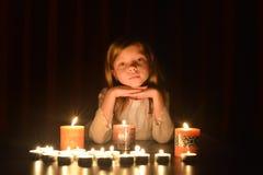 Het leuke kleine blondemeisje houdt haar handen onder de kin Veel kaarsen zijn rond haar, over donkere achtergrond stock fotografie