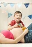 Het leuke kleine jongen spelen op de buik van de moeder stock afbeelding