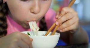 Het leuke kleine kind zit bij een lijst en eet zijn noedels, gewillig eet de baby Meisje die noedels eten met stock videobeelden