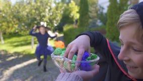 Het leuke kleine kinderen spelen bedriegt of behandelt spel op Halloween-vooravond, buur POV stock video