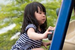 Het leuke meisje beklimt omhoog op ladder in speelplaats stock afbeeldingen