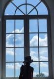 Het leuke meisje bevindt zich dichtbij een venster en bekijkt de hemel met wolken stock afbeelding