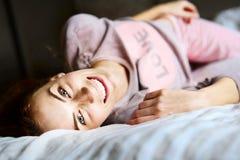 Het leuke meisje bij slaapkamer bekijkt de camera Stock Foto's